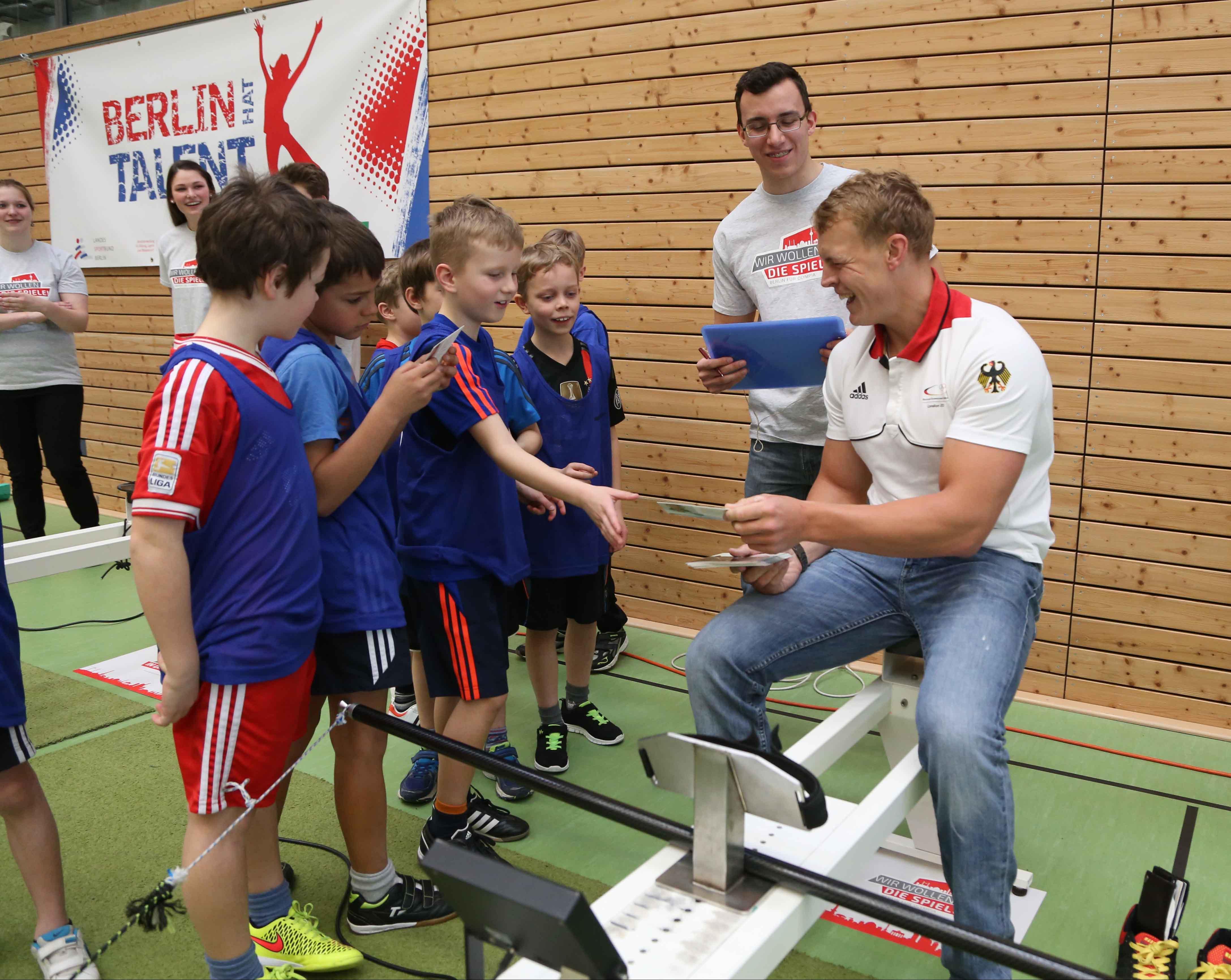 Kanu-Weltmeister Marcus Gross scherzt mit Kindern auf der Talentiade in Köpenick