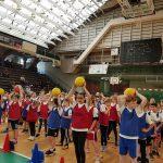 Kinder spielen ein Staffelspiel mit einem Basketball