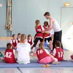 Trainer zeigt Kindern die richtige Judo-Technik