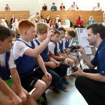 Trainer erklärt Kindern die Schlittschuhe