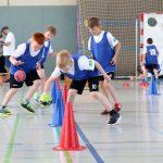 Kinder durchlaufen einen Handball-Parcour