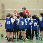 Kinder greifen nach Volleyball