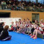 Kinder hören den Ringen-Übungsleiterinnen zu