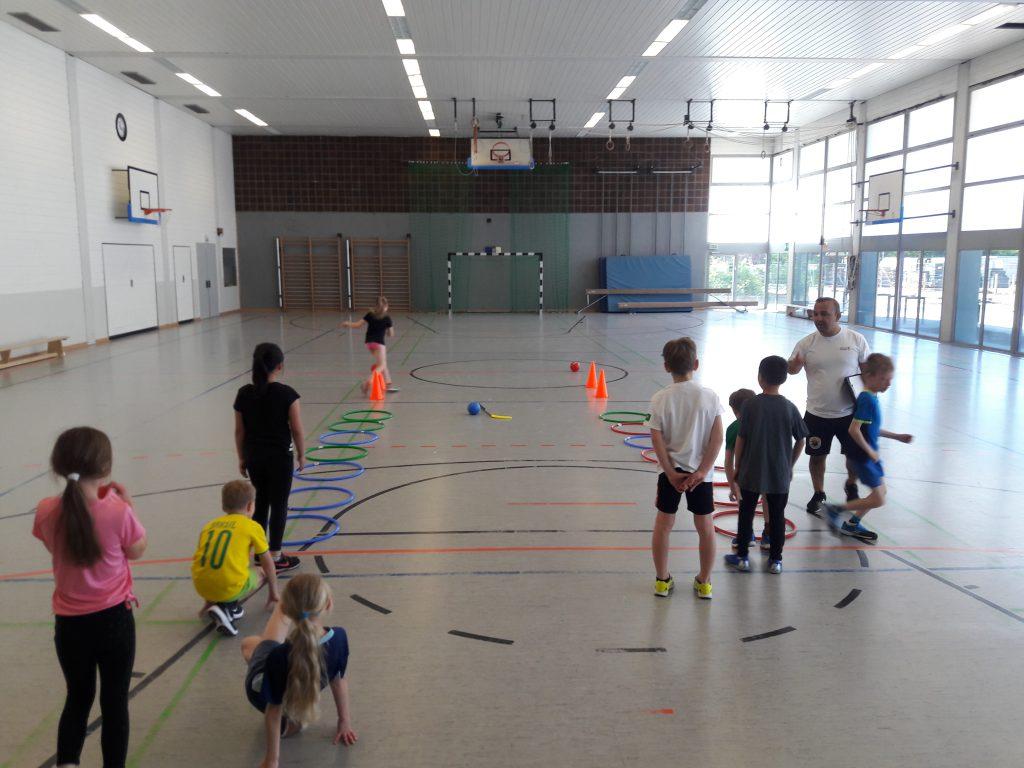 Die Kinder probieren die ersten Übungen mit den neuen Sportmaterialien. Mit Sinan Hanli