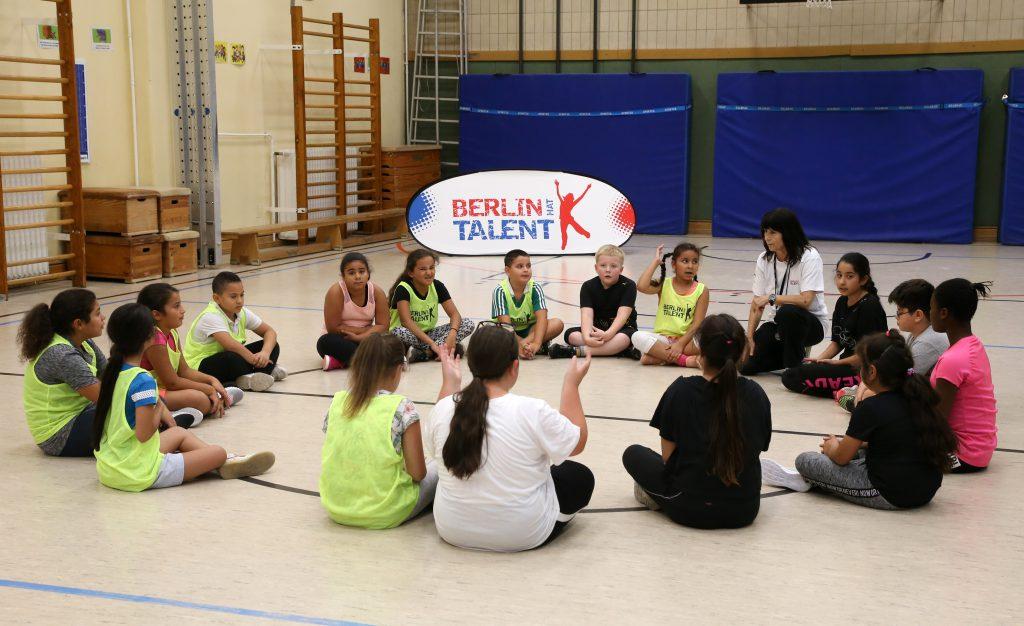 Kinder sitzen mit Ihrer Lehrerin im Kreis